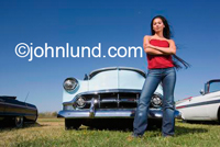 Picture of a beautiful Latina woman standing tall and proud with long black hair in front of a vintage show car. She is semi smiling with her arms crossed in front of her.
